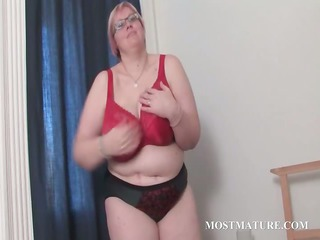Mature BBW in glasses works her huge tits in bed